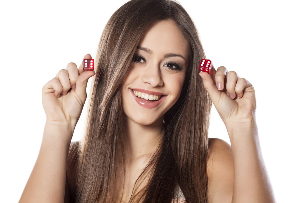 smiling girl holding a pair of dice for gambling